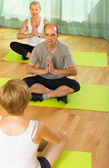 Mature couple practicing yoga with instructor — Foto de Stock