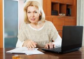 Woman with laptop and financial documents — Stock Photo