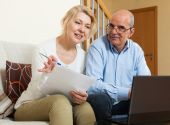 Mature couple with documents and notebook — Stock Photo