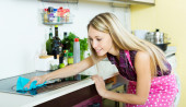 Maid cleans modern stove — Zdjęcie stockowe