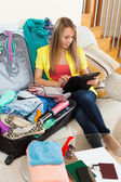 Girl sitting on sofa near luggage — Stock Photo