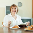Mature woman having breakfast — Stock Photo #64292255
