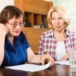 Sad elderly women reading documents — Stock Photo #64297019