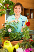 Elderly woman with fresh flowers — Stock Photo