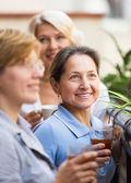 Three women drinking tea at balcony — Stock Photo
