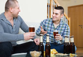 Two friends drinking beer at home — Stock Photo