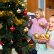 Happy children decorating a fir — Foto Stock #64303433