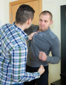 Two adult males fighting indoor — Stock Photo