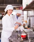 Chef and his helper at kitchen — Stock Photo