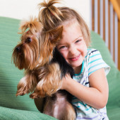 Happy child holding Yorkshire Terrier — Stock Photo