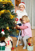 Sisters hanging decorations on fir — Stock Photo