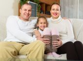 Happy couple with daughter at home — Stock Photo