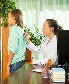 Doctor with stethoscope examining teenage boy — Stock Photo