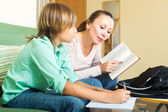Mother dictating and son writing — Stock Photo