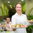 Waitress serving food to visitors — Stock Photo #64330939