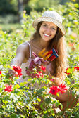 Chica en planta de rosas en el jardín — Foto de Stock