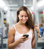Woman using smartphone in subway — Stock Photo