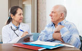 Man complaining to doctor about heartache — Stock Photo