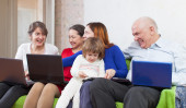 Happy family with laptops at home — Stock Photo