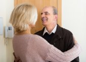 Mature wife meeting husband near door — Stock Photo