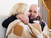 Spouses under blanket drinking tea — Stock Photo