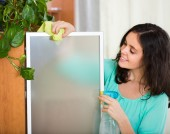 Woman dusting glass of furniture — Stock Photo