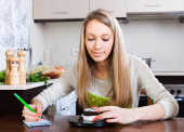 Girl weighing cakes on kitchen scales   — Stock Photo