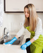 Blonde woman in apron cleaning kitchen   — Stock Photo