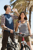 Couple with bicycles drink water — Stock Photo
