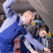 Постер, плакат: Car mechanics working at carshop
