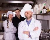 Hospitable chef and two helpers — Stock Photo
