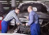 Car mechanics  working at carshop — Stock Photo
