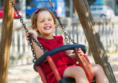Laughing girl  on chain swing — Stock Photo