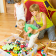Children and mother collecting toys — Stock Photo #66617133