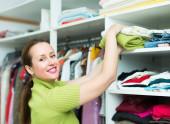 Woman arranging clothes at wardrobe — Stock Photo