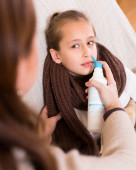 Woman treating daughter for rhinitis — Stock Photo