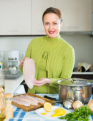 Cheerful female cooking fish — Stock Photo