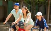 Cheerful family cycling on city street — Stock Photo