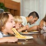 Family of four eating spaghetti — Stock Photo #66646529