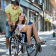 Girl in wheelchair with friend outdoor — Stock Photo #66649615
