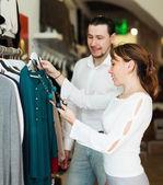 Man and woman choosing clothes at shop — Stock Photo