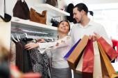 Młoda para wybierając ubrania w sklepie — Zdjęcie stockowe