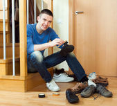 Happy man cleaning boots — Stockfoto