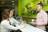 Bartender and smiling women at bar — Stock Photo