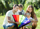 Girls and parents playing with kite — Stock Photo