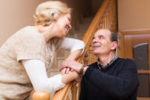 Happy spouses leaning against stairway — Stock Photo