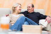 Mature couple on couch at home — Stock Photo