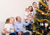Family decorating New Year tree — Stock Photo