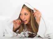 Woman eating  chocolate  in bed — Stock Photo