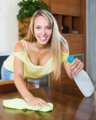 Young smiling girl dusting table — Stock Photo